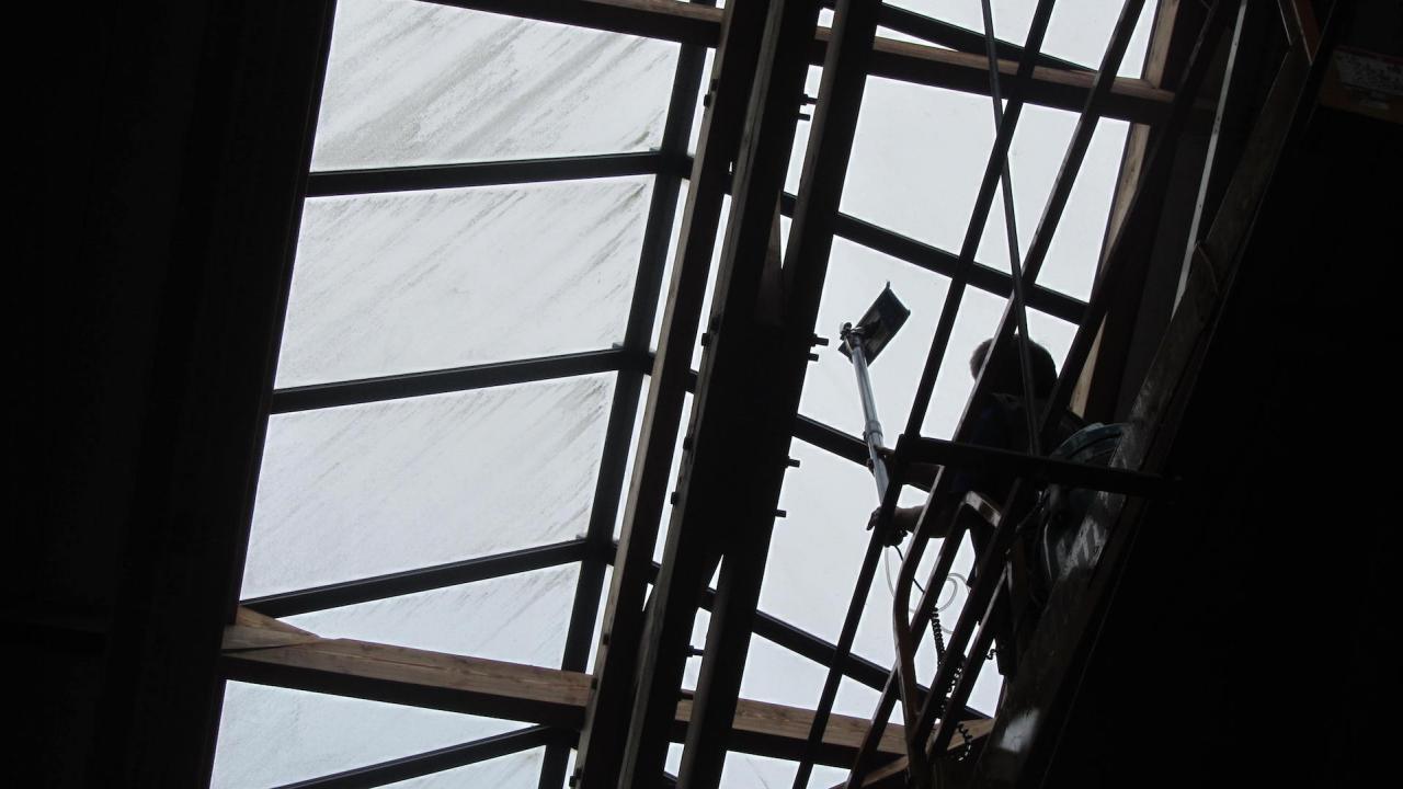 Nettoyage des vitres de toiture entre la charpente